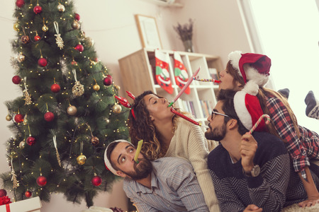 Group of young frineds lying on the floor next to a Christmas tree, having fun blowing party whistles 스톡 콘텐츠