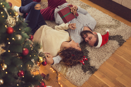 High angle view of a beautiful young couple lying on the living room floor next to a nicely decorated Christmas tree, exchanging Christmas presents