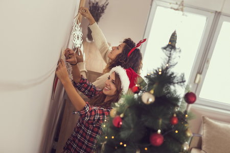 Two beautiful young women decorating home for Christmas and having fun