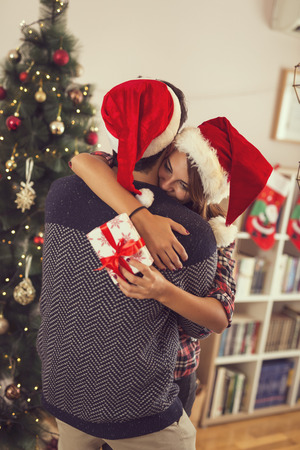 Loving couple hugging and exchanging presents on a Christmas morning