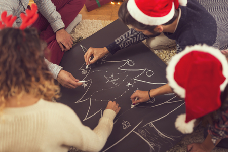 High angle view of a group of friends having fun drawing a Christmas tree with a white chalk on huge piece of black paper. Selective focus on the mans hand