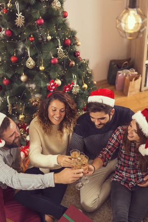 High angle view of a group of friends sitting on the floor next to a Christmas tree, making a toast