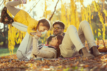 Young family enjoying a beautiful autumn day in nature, having a picnic and spending time together; mother lifting her daughter. Focus on the mother