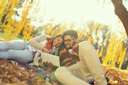 Couple in love lying on a picnic blanket in a park, enjoying beautiful autumn day in nature and taking selfie. Focus on the girl