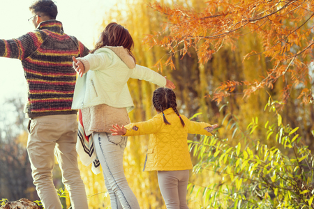 Young mother, father and daughter walking down the park, having fun and enjoying a beautiful autumn day in nature. Focus on the daughter 스톡 콘텐츠