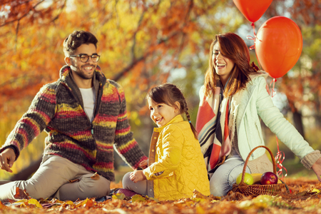 Young mother, father and daughter having fun, throwing colorful autumn leaves and enjoying beautiful autumn day in nature 스톡 콘텐츠
