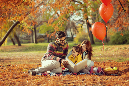 Mother, father and daughter having fun on an autumn picnic in park, sitting on a picnic blanket and reading a story