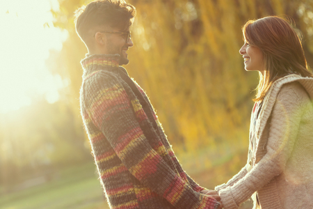 Young couple in love holding hands, looking each other and standing in the park on a sunny autumn day