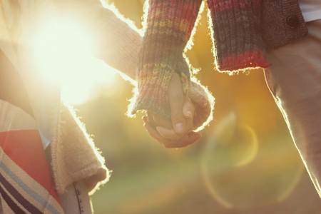 Detail of a young couple in love holding hands and walking through a park on a sunny autumn day 스톡 콘텐츠