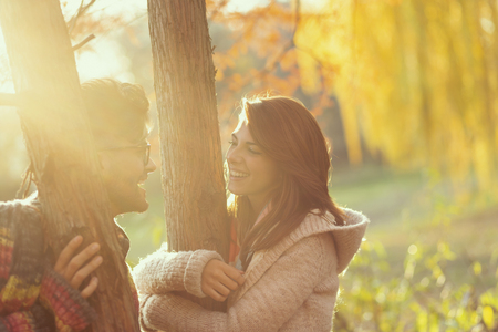 Young couple in love standing in the park next to a tree, hugging the tree branches and enjoying beautiful autumn sunny day in the park