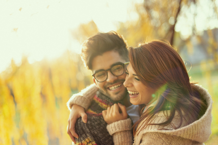 Young couple in love hugging, having fun and smiling in the park on a sunny autumn day 스톡 콘텐츠