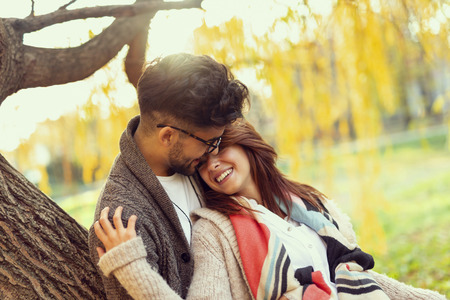 Young couple in love leaning on a tree in the park, hugging and enjoying beautiful sunny autumn day. Focus on the guy