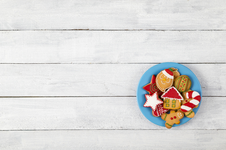 Top view of a plate of nicely decorated gingerbread Christmas cookies on white wooden background