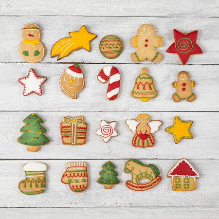 Top view of different shapes of nicely decorated gingerbread Christmas cookies on wooden background 스톡 콘텐츠
