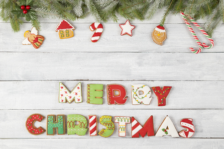 Top view of nicely decorated gingerbread Christmas cookies shaped as letters Merry Christmas with pine branches, candy cane and mistletoe on white wooden background 스톡 콘텐츠