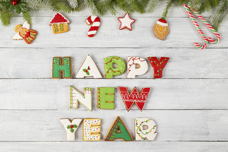 Top view of nicely decorated colorful gingerbread Christmas cookies shaped like letters Happy New Year with pine branches and candy cane on wooden background