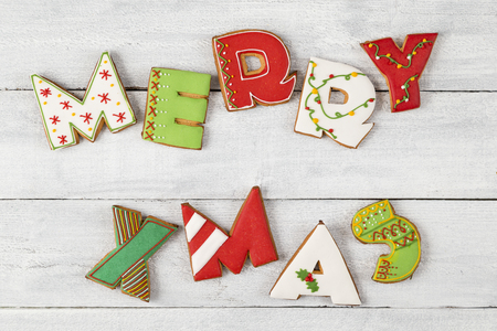 Top view of colorful, nicely decorated gingerbread Christmas cookies shaped as letters Merry Xmas on white wooden background 스톡 콘텐츠