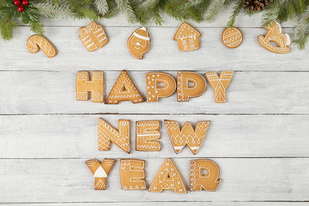 Table top shot of gingerbread cookies shaped as letters Happy New Year with some fir branches, pine cones and a mistletoe