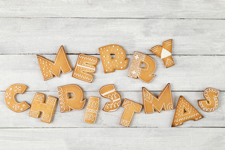 Top view of nicely decorated gingerbread Christmas cookies shaped as letters Merry Christmas on white wooden background