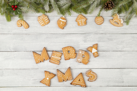 Top view of nicely decorated gingerbread Christmas cookies shaped as letters Merry Xmas with pine branches, candy cane and mistletoe on white wooden background