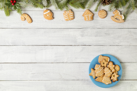 Table top shot of a plate of nicely decorated gingerbread Christmas cookies on white wooden background decorated with fir branches, mistletoe and pine cones 스톡 콘텐츠