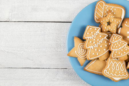 Table top shot of a plate of nicely decorated gingerbread Christmas cookies on white wooden background