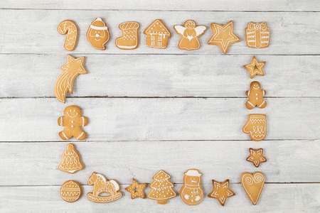 Top view of a frame made of nicely decorated gingerbread Christmas cookies with copy space in it on white wooden background