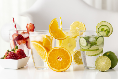 Glasses of infused water with fresh strawberries, lime, cucumber and mint leaves, lemon and orange. Focus on the orange slice on the glass