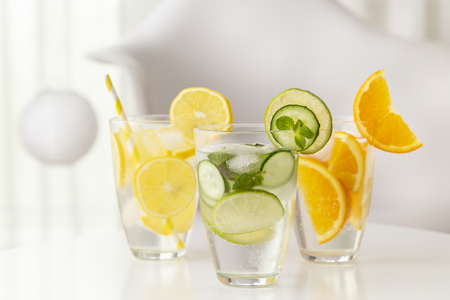 Glasses of infused water with fresh lime, cucumber and mint leaves, lemon and orange