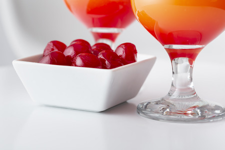 Detail of two cold tequila sunrise cocktails with tequila, pomegranate juice and orange juice decorated with slices of orange and maraschino cherries. Selective focus on the cherries