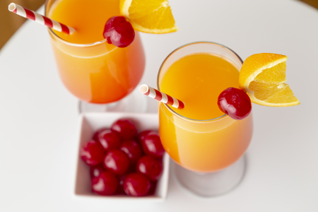 High angle view of two cold tequila sunrise cocktails with tequila, pomegranate juice and orange juice decorated with slices of orange and maraschino cherries. Focus on the cherry on the glass