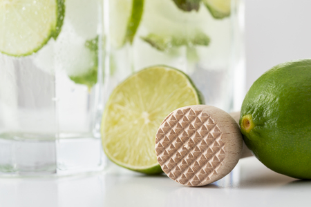 Detail of two mojito cocktails with lots of ice, white rum, lemon juice and tonic, decorated with lime slices and mint leaves on a modern white table. Selective focus on the ice crusher 스톡 콘텐츠