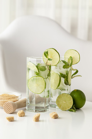 Two mojito cocktails with lots of ice, white rum, lemon juice and tonic, decorated with lime slices and mint leaves on a modern white table
