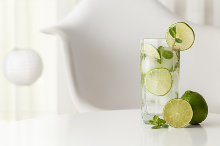 Mojito cocktail with lots of ice, white rum, lemon juice and tonic, decorated with lime slices and mint leaves on a modern white table with fresh lime and mint leaves next to it