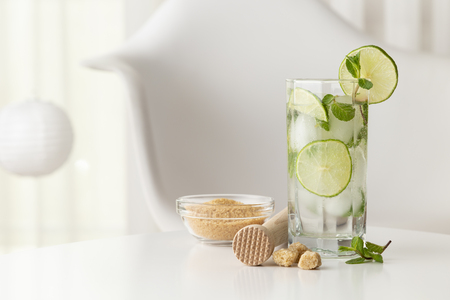 Mojito cocktail with lots of ice, white rum, lemon juice and tonic, decorated with lime slices and mint leaves on a modern white table with ice crusher and bowl of brown sugar next to it Stok Fotoğraf