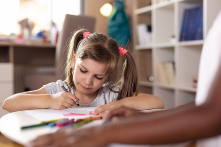 Two little girls sitting on a playroom floor, drawing with crayons, finishing their art project for school