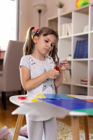 Little girl playing in a playroom, cutting colourful paper, making decorations for an art project for school and having fun Zdjęcie Seryjne