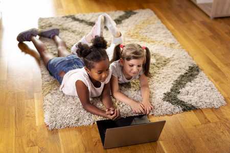 Two little girls lying on the playroom floor, watching cartoons on a laptop computer and having fun.