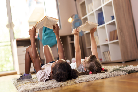 Two little girls lying on the playroom floor, reading books for school. Zdjęcie Seryjne