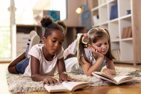Two little girls lying on the playroom floor, reading books for school, studying.