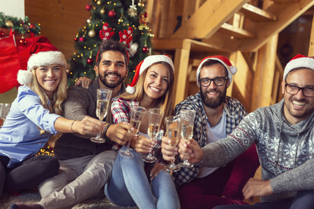 Group of friends sitting on the floor next to a nicely decorated Christmas tree and making a toast with glasses of champagne. Zdjęcie Seryjne