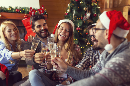 Group of friends sitting on the floor next to a nicely decorated Christmas tree and making a toast with glasses of champagne. Focus on the girl in the middle