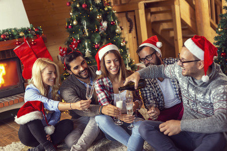 Group of friends sitting on the floor next to a nicely decorated Christmas tree, pouring champagne into glasses and making a toast