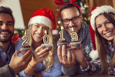 Group of young friends celebrating Christmas, holding cupcakes with lit candles shaped like numbers 2019. Focus on the candles