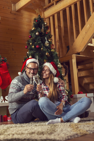 Beautiful couple in love, wearing santa hats, sitting next to a nicely decorated Christmas tree and making a toast with glasses of champagne.
