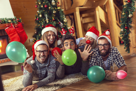 Group of friends lying next to a fireplace and Christmas tree, having fun on Christmas morning, blowing colorful balloons and decorating the house