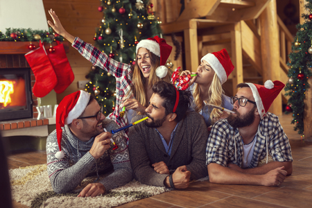 Group of friends lying next to a fireplace and a nicely decorated Christmas tree, blowing party whistles and having fun on Christmas morning