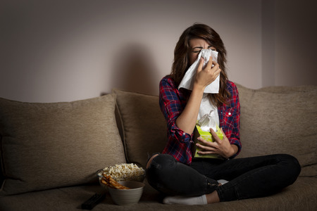 Beautiful young woman sitting in the dark on a living room couch, watching a soap opera, blowing her nose and crying