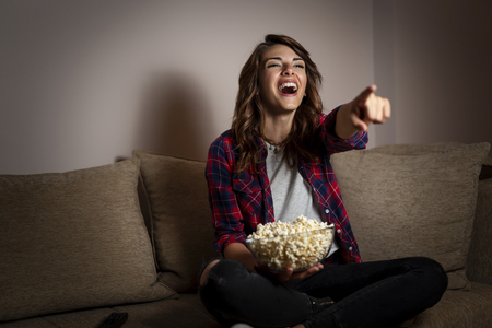 Beautiful young woman sitting in the dark on a living room couch, having fun watching a comedy on TV and eating popcorn