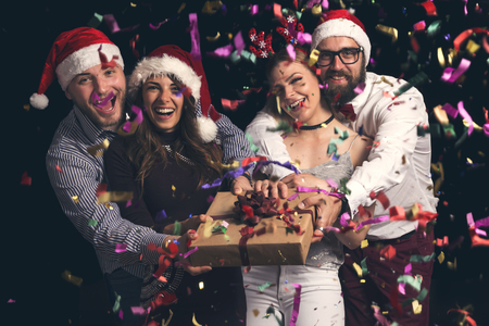 Two beautiful young couples wearing Santa hats, having fun at New Years party and holding nicely wrapped present box